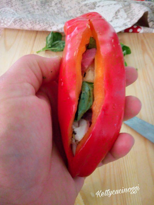 Una volta pronti tutti gli ingredienti possiamo procedere per la farcitura dei <b>peperoni cornetto</b>.  Per prima cosa con un coltello affilato facciamo un taglio sul peperone, quindi all'interno mettiamo l'aglio, la pancetta, il pecorino e per ultimo il basilico.
