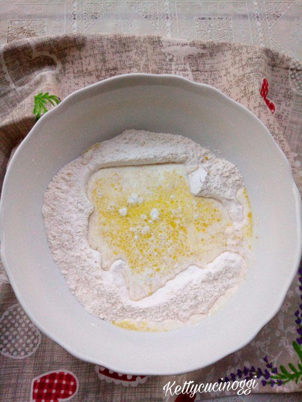 Quando abbiamo tutti gli ingredienti pronti procediamo a preparare il pane. In una ciotola versiamo tutti i componenti secchi, quindi le farine ,il sale, lo zucchero e il bicarbonato e mescoliamo il tutto. Dentro la brocca del latticello invece aggiungiamo l'olio e versiamo il tutto dove abbiamo gli ingredienti secchi.