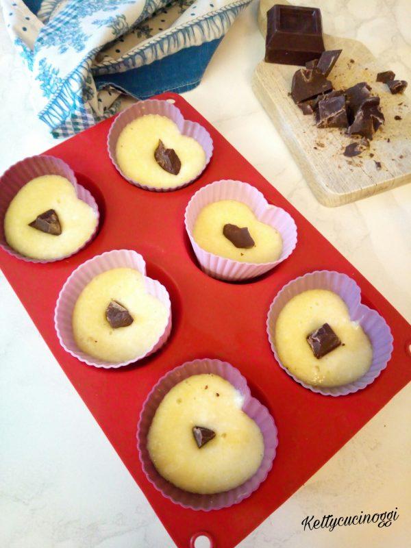 Una volta pronto l'impasto dei <b> Muffin</b> prepariamo gli stampini e facendoci aiutare con un cucchiaio versiamo un po' di composto nello stampino, aggiungiamo un pezzetto di cioccolato fondente.