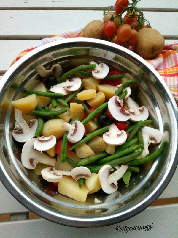 Una volta pronti tutti gli ingredienti possiamo assemblare la nostra <i><b>Insalata estiva al pesto</b></i>, mettendo le patate tagliate, i fagiolini, i pomodorini i funghi e le olive nere, pepiamo e saliamo se necessita e condiamo con l'emulsione del pesto e mettiamo nel piatto da portata.