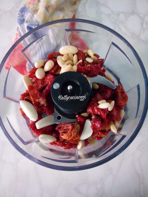 Nel mixer o frullatore mettiamo per prima cosa  i <i>Pomodori secchi</i> con le mandorle i pinoli e l'aglio, azioniamo e lasciamo frullare per qualche minuto.