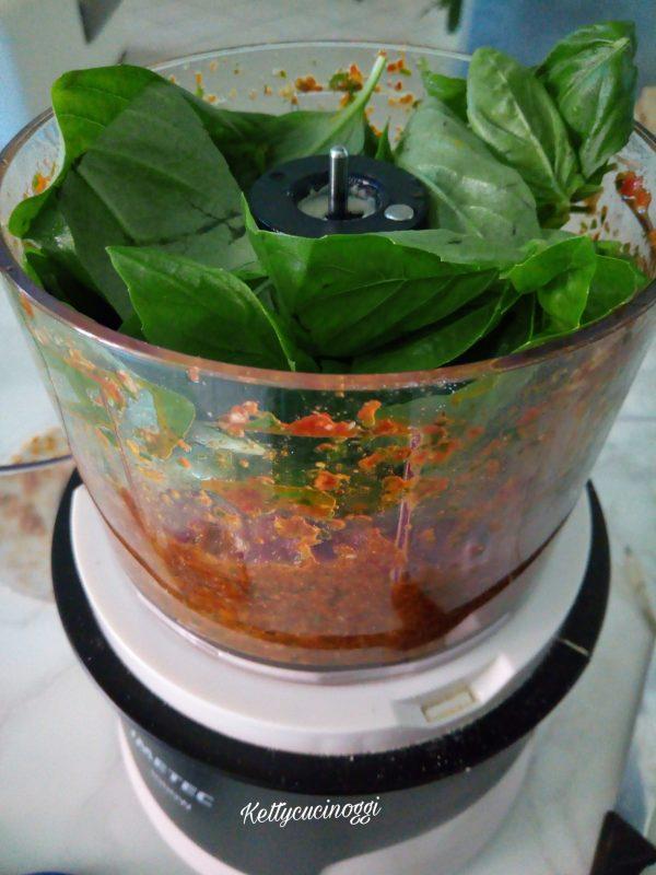 Adesso aggiungiamo le foglie di basilico e il formaggio grattugiato e mettiamo lentamente l'olio extravergine di oliva.