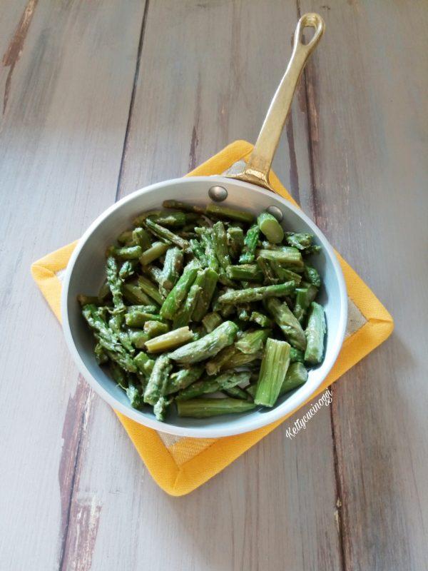 In una padella, mettiamo il cucchiaio di olio e facciamo rosolare l'aglio una volta lo togliamo e pronto mettiamo le punte degli asparagi leggermente lessati in precedenza, saliamo e pepiamo e lasciamo insaporire per 10 minuti, e una volta pronti li lasciamo raffreddare.