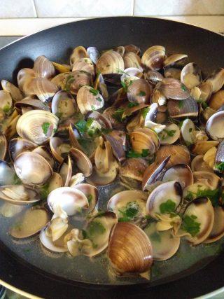 In una padella mettiamo l'aglio tritato finemente il peperoncino e il prezzemolo, lasciamo rosolare bene il tutto e aggiungiamo le <b>Vongole</b>, sfumiamo con il vino bianco e copriamo sino a quando le <b>Vongole</b> non si saranno aperte tutte.