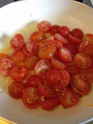 In un'altra padella facciamo rosolare uno spicchio di aglio schiacciato, una volta pronto lo togliamo e aggiungiamo i pomodorini, lasciamo cuocere per circa 5/7 minuti.