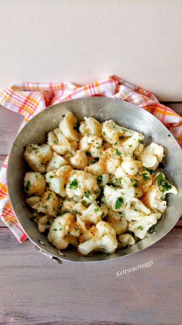 Scoliamo il <b>Cavolfiore</b> e lo mettiamo dentro una teglia o pirofila condiamo con olio extravergine di oliva, pepiamo, aggiungiamo il formaggio grattugiato il pane tostato e lo spicchio di aglio intero schiacciato, mescoliamo il tutto e per ultimo mettiamo il prezzemolo tritato, e ancora del pane tostato.