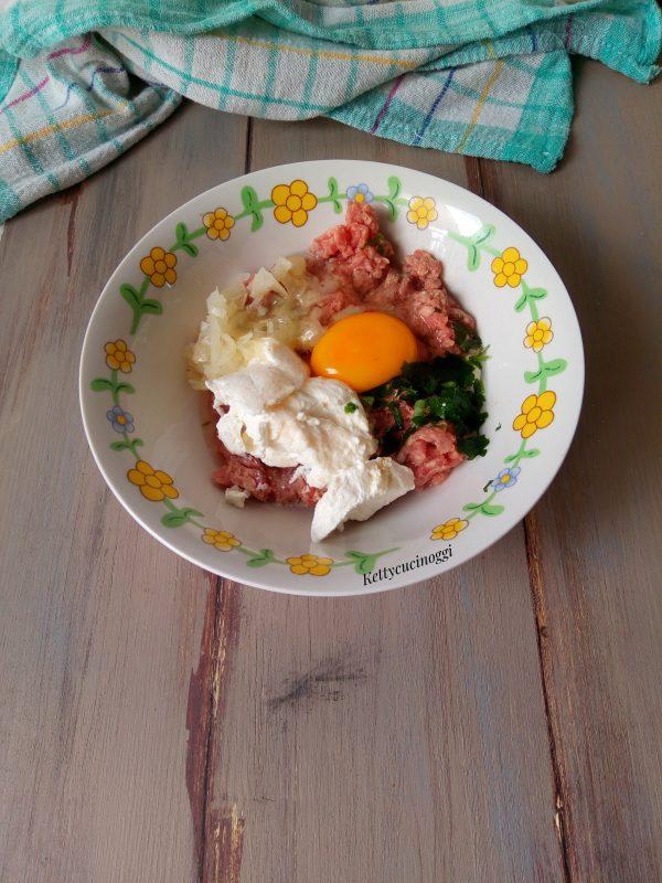 In una ciotola mettiamo la carne macinata, l'uovo, la ricotta, il prezzemolo tritato e per ultimo la cipolla, saliamo e pepiamo. Amalgamiamo bene il tutto.