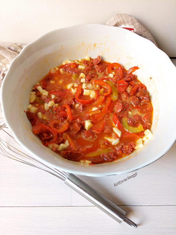 In una ampia ciotola sbattiamo le uova e aggiungiamo il nostro condimento per farcire <i><b>Torta salata al chorizo con patate e peperoni</b></i>  per ultimo grattugiamo la provola e mescoliamo bene il tutto.