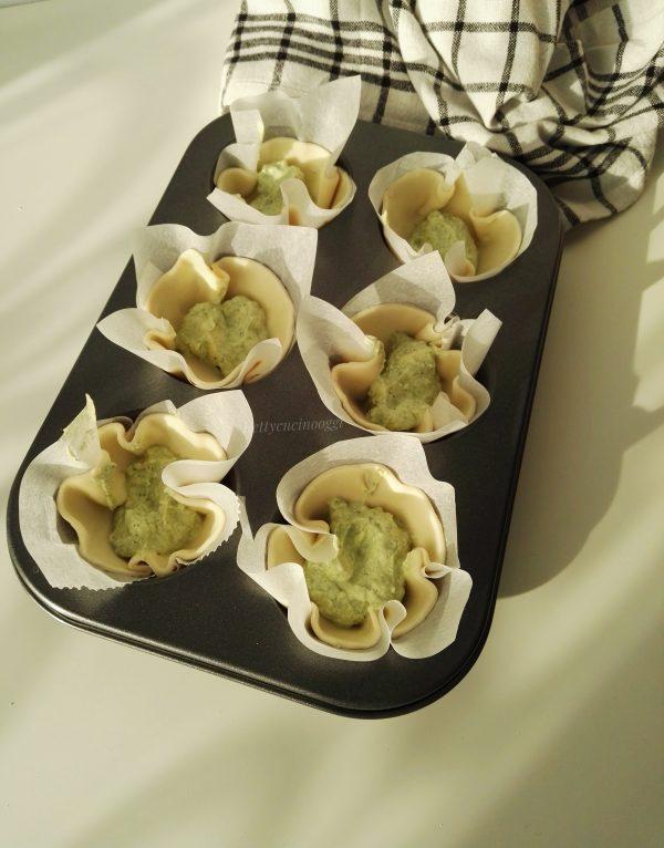 Inseriamo in uno stampo da muffin i cerchi facendo spazio in centro, mettiamo un cucchiaio di crema di <b>pesto</b>.