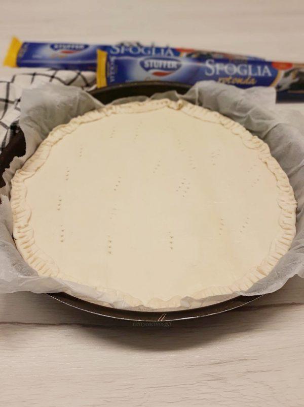 In una teglia dal diametro 22 ricoperta da carta a forno sovrapponiamo i due dischi di pasta  di pasta sfoglia <b>stuffer</b> , pizzichiamo verso l'interno il bordo di pasta formando una sorta di cordoncino e bucherelliamo.