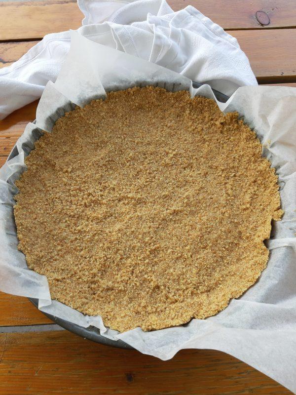 In una teglia da crostata diametro 25, copriamo con la carta a forno, e con il dorso di un cucchiaio compattiamo bene la base.
