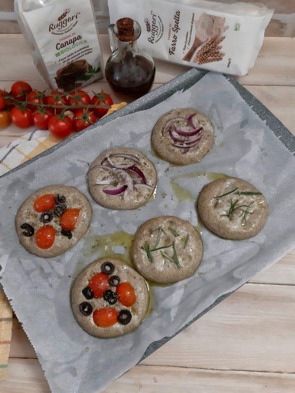 Condiamo con pomodorini e olive nere e origano, su altre mettiamo delle fette di cipolla di tropea, altre focaccine solo rosmarino, infine fiocchi  di sale grosso su ognuno di loro.